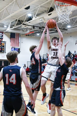 Liberty Union junior Jacob Denney goes up for a shot between Morgan's Colin James and Jason Wells as Carver Myers looks on. The Raiders topped the Lions, 70-55.