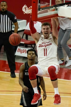Wisconsin's Micah Potter throws down a dunk during the second half against Minnesota.