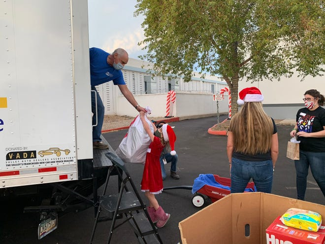 On Dec. 8, donors dropped off toys at Arizona Helping Hands for foster children, including this small elf, to fill Santa's sleigh (a 20-foot box truck).