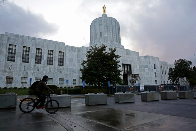 A man rides a bicycle past newly installed cement blocks placed outside the Oregon State Capitol Building in Salem, Oregon, on Wednesday, Dec. 30, 2020.