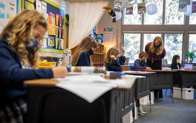 A teacher at All Saints' Day School looks at a student's work during an in-person lesson in Carmel, Calif., on Thursday, Dec. 10, 2020.