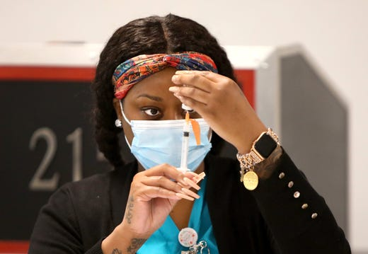 Nurse Shanteria Johnson, who is with the Medical Reserve Core at the Alachua County Health Department, draws a dose of the Moderna COVID-19 vaccine during a vaccination session for local firefighters at the Gainesville Professional Firefighters Union Hall in Gainesville Fla., Dec. 31, 2020.