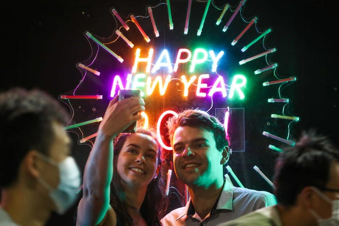 People seen having their photo taken in front of a neon Happy New Year sign as people wearing masks walk past during New Year's Eve celebrations on December 31, 2020 in Melbourne, Australia. Celebrations look different this year as COVID-19 restrictions remain in place due to the ongoing coronavirus pandemic.