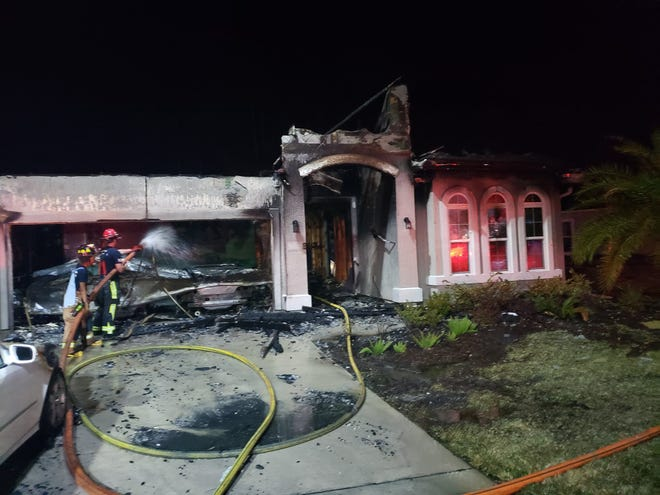 Clay County firefighters hose down an Oakleaf  home that was destroyed following a blaze that was started by discarded New Year's Eve fireworks.