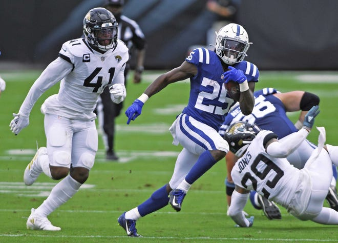 Jaguars defensive end Josh Allen tries to chase down Indianapolis Colts running back Marlon Mack as he scrambles for yardage. Both players are out because of injuries.