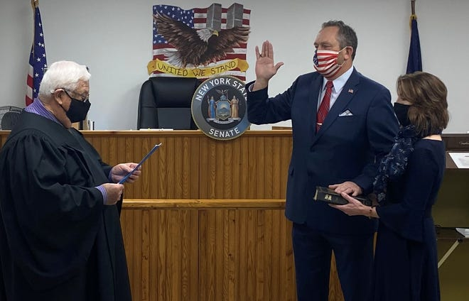 State Sen. Peter Oberacker with his wife, Shannon, takes the oath of office at the Town of Maryland Courthouse.  From left, Town of Maryland Justice Joseph Staruck, Sen. Peter Oberacker and Shannon Oberacker.