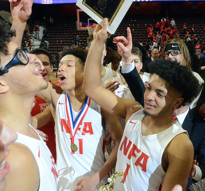 NFA's Mason Jackson, left, Jared Martin and Xavier Marquez celebrate their ECC Division I championship victory at the Mohegan Sun Arena.