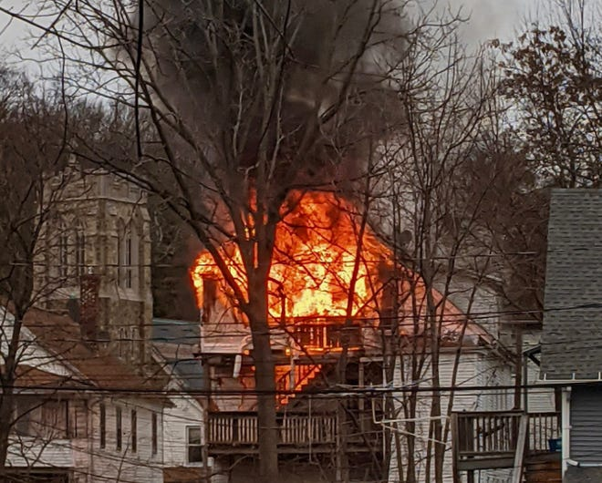 Flames fill the top floor of a house on Abbott Place. Blessed Sacrament Church, also in photo, is a block away.