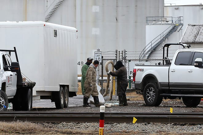 Workers clean up the aftermath of a Dec. 30, 2020 gasoline release from a Magellan Midstream Partners storage and distribution terminal on U.S. Highway 71 in Fort Smith on Friday, Jan. 1, 2021. The Environmental Protection Agency and Arkansas Department of Environmental Quality were notified about the incident.
