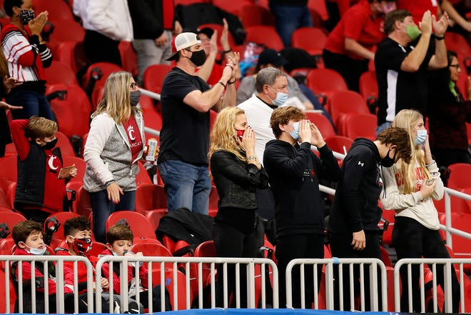 The Fickell family cheers on a third down in the second quarter of the Chick-fil-a Peach Bowl at Mercedes-Benz Stadium in Atlanta on Friday, Jan. 1, 2021. The Bearcats led 14-10 at halftime.
