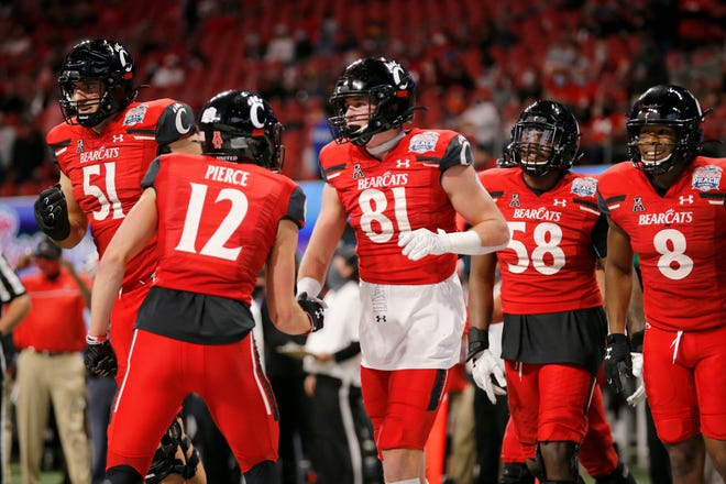 The Cincinnati Bearcats celebrate a touchdown catch by tight end Josh Whyle (81) in the second quarter of the Chick-fil-a Peach Bowl at Mercedes-Benz Stadium in Atlanta on Friday, Jan. 1, 2021. The Bearcats led 14-10 at halftime.