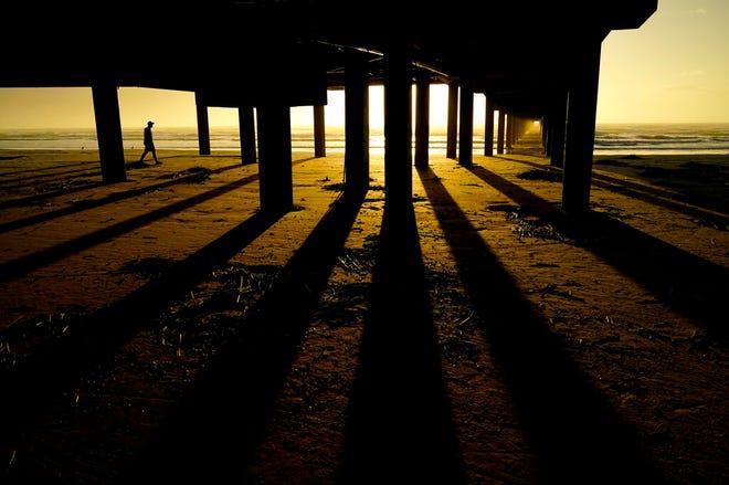Dalam file foto 21 November 2020 ini, seorang pria berjalan di sepanjang pantai di bawah Dermaga Horace Caldwell saat matahari terbit di Port Aransas, Texas.