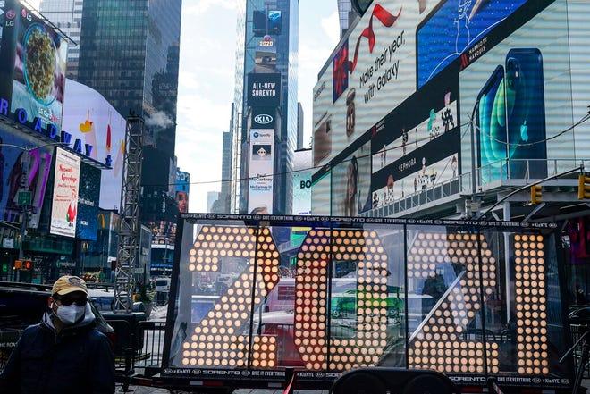 """Dalam file foto 21 Desember 2020 ini, seorang pria berjalan melewati angka raksasa untuk """"2021"""" untuk digunakan dalam perayaan malam Tahun Baru mendatang di Times Square New York."""