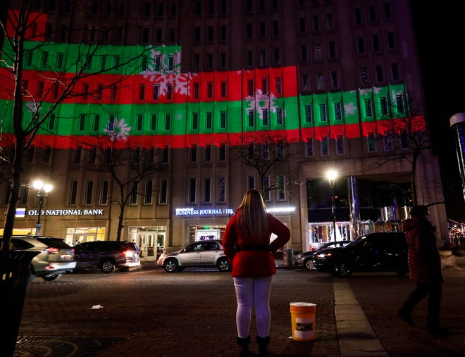 People gather in downtown Indianapolis at Monument Circle and walk to bars to celebrate New Years Eve on December 31, 2020. All bars in Marion County must be closed before midnight due to restrictions COVID-19 from the Marion County Health Department.