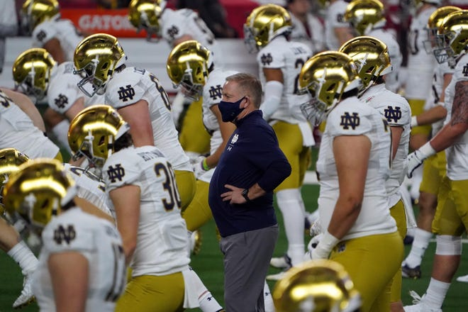 Notre Dame Fighting Irish head coach Brian Kelly stands on the field before the Rose Bowl against the Alabama Crimson Tide at AT&T Stadium.