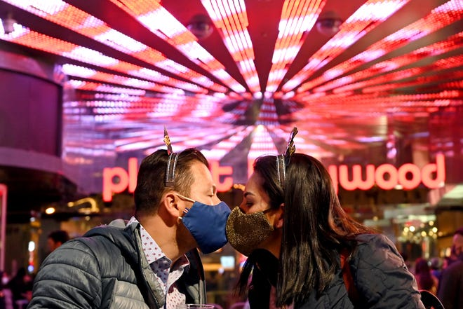 A couple kiss as they celebrate New Year's Eve along the Las Vegas Strip Thursday, Dec 31, 2020, in Las Vegas.