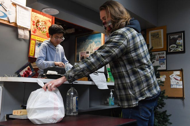 Justin Stevenson picks up a to-go order on Thursday, December 31, from Pho Quynh in Sioux Falls.