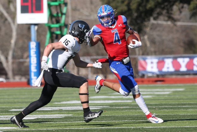 Hays running back Michael Boudoin runs the ball past Vandegrift junior Reece Beauchamp during the Rebels' 38-10 win in the Class 6A Division II Region IV final Saturday in Buda. Hays will face Katy in next weekend's state semifinals.