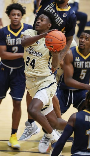 University of Akron forward Ali Ali goes to the basket against Kent State's Malique Jacobs and Danny Pippen II during the Zips' 66-62 win Friday night at Rhodes Arena. [Mike Cardew/Beacon Journal]