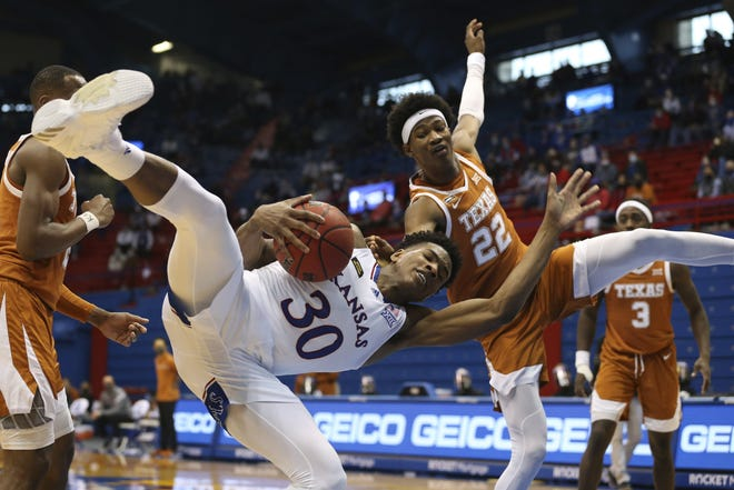 Kansas guard Ochai Agbaji holds on to a rebound against Texas forward Kai Jones in the second half of Saturday's 84-59 win in Lawrence, Kan. It matched the biggest margin of victory against Kansas in Lawrence since 1955.