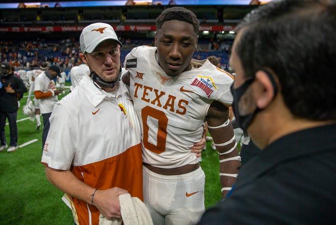 Texas football coach Tom Herman hugs linebacker DeMarvion Overshown after the Longhorns beat Colorado in the Alamo Bowl in San Antonio on Dec. 29, 2020.