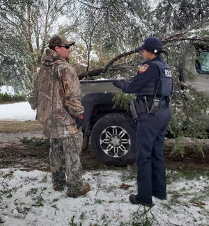 Off-duty Early firefighter Jay Wilder and officer Tasha Tobias stand next to Debra Mathis' pickup Friday morning. Three large tree branches broke off and fell onto the truck. Tobias and Wilder, along with other off-duty firefighters, showed up to help after Mathis called 9-1-1 to explain her situation.