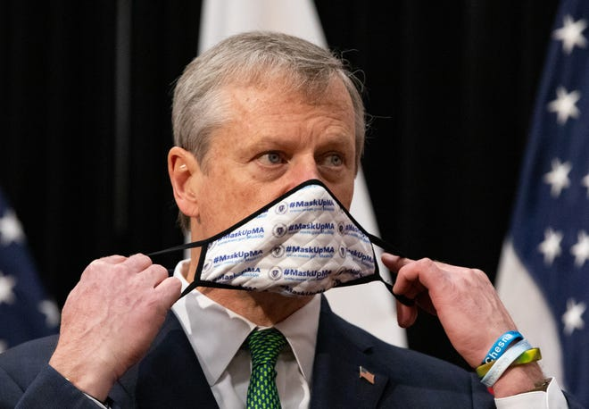 Gov. Charlie Baker pulls on a mask, branded with the state's #MaskUpMA slogan, after announcing a series of reopening rollbacks and other measures such as tightened face mask requirements on Dec. 8.