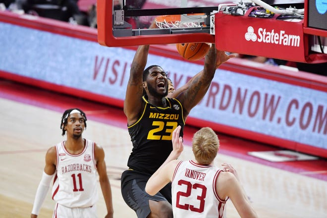 Missouri forward Jeremiah Tilmon (23) dunks the ball over Arkansas defenders Jalen Tate (11) and Connor Vanover (23) during a game Saturday in Fayetteville, Ark.