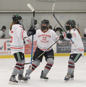 Whitman-Hanson/ Silver Lake's Shea Kelleher, left, scored a goal and was congratulated by teammates Kendyl Peterson,center, and Caleigh Tompkins,  versus Quincy/North Quincy, Saturday, Jan. 2, 2021. Game ended in a 4-4 tie at the Bog Arena in Kingston.