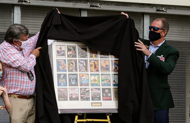 Retired TaxSlayer Gator Bowl president Rick Catlett unveils a plaque with the program covers of the 28 games he presided over during a halftime ceremony on Saturday.