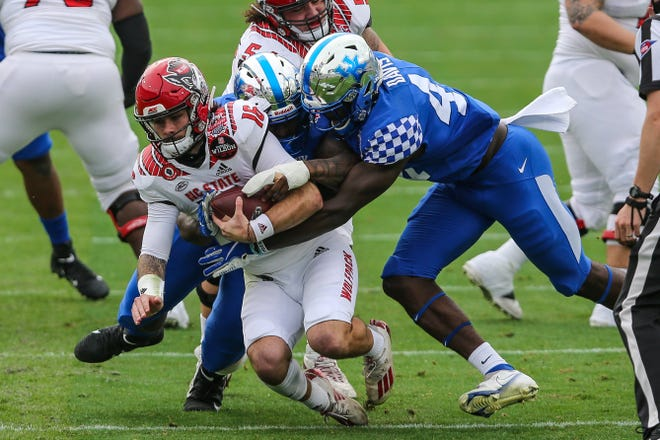 NC State quarterback Bailey Hockman (16) is sacked by Kentucky linebacker Jamin Davis (44) during the first half of the TaxSlayer Gator Bowl.