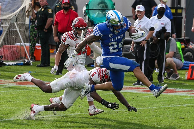 Kentucky running back Chris Rodriguez Jr. (24) runs the ball for a touchdown, escaping NC State safety Jakeen Harris (6), left, and cornerback Isaac Duffy (33) during the second half of the TaxSlayer Gator Bowl Saturday.