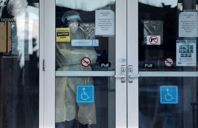 A staff member with personal protective equipment looks out from the front entry door of the Illinois Veterans Home in LaSalle on Dec. 3, 2020. At least 33 veterans at the facility have been killed by the virus.