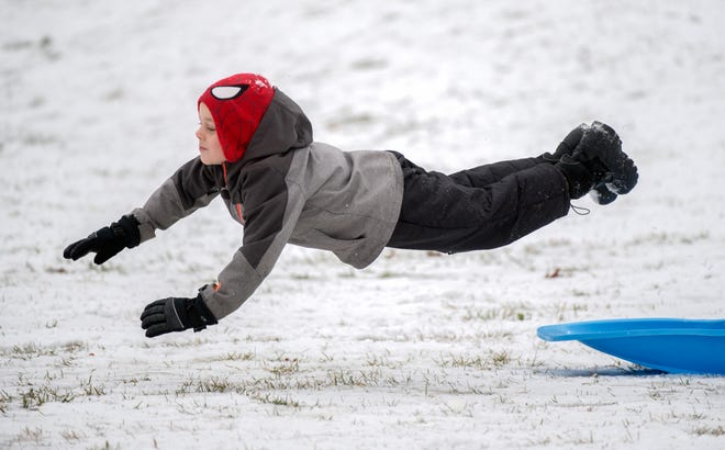 Nolan Meints, 6, of Peoria goes airborne while trying to stand on his sled down a hill Saturday at Bradley Park in Peoria. Families hit the slopes throughout the Peoria area after snow and ice blanketed central Illinois.