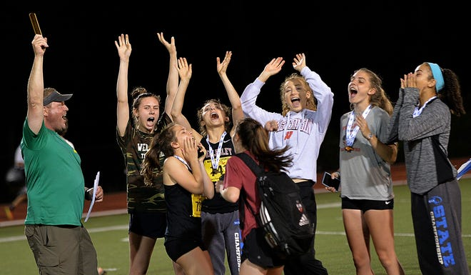 The Wellesley girls track team, and head coach John Griffith (left), celebrate after the public address announcer announced that they had won the MIAA All-State track team state championship in 2018 at Fitchburg State.