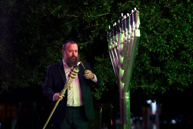Rabbi Zalman Levitin lights a torch for the menorah lighting during the Chabad House's Chanukah on Worth in 2019.