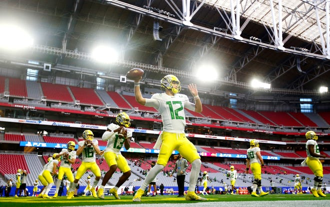 Oregon quarterback Tyler Shough (12) throws passes before the Fiesta Bowl game against Iowa State at State Farm Stadium.
