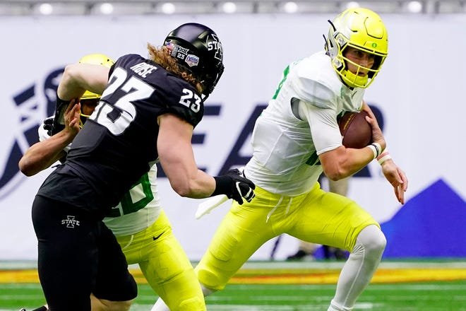 Oregon quarterback Tyler Shough scrambles away from Iowa State linebacker Mike Rose (23) during the first half of the Jan. 2 Fiesta Bowl in Glendale, Ariz.