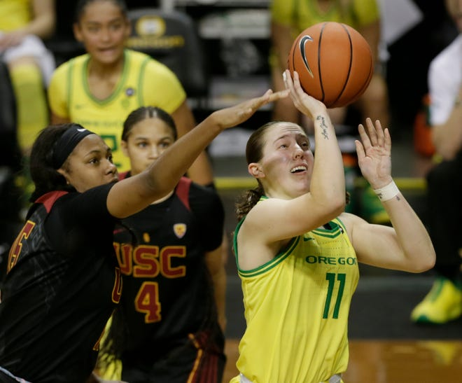 Oregon's Taylor Mikesell, right, shoots ahead of the USC defense during the second half.
