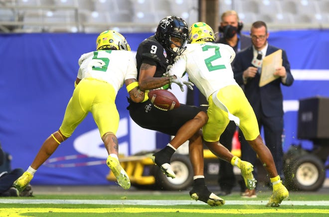 Oregon's Kayvon Thibodeaux (5) and Mykael Wright (2) break up a pass to Iowa State Cyclones wide receiver Joe Scates during the first half of the Jan. 2 Fiesta Bowl at State Farm Stadium in Glendale, Ariz.