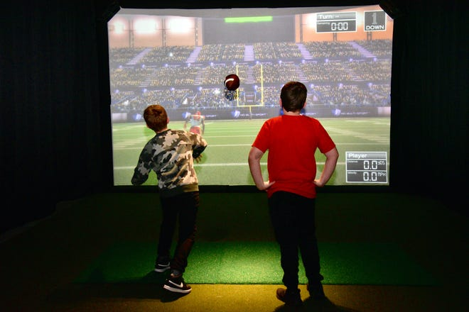 Jakub Brooks, 12, throws the football as his cousin Jaycer Hake, 12, watches during the football game on the Sport Simulator at the District Eat and Play Salina at Central Mall on Thursday evening.
