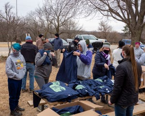 Several of the 60 people who took part in the Kanopolis State Park First Day Hike pick up their free T-shirts before heading to the trails on Friday.