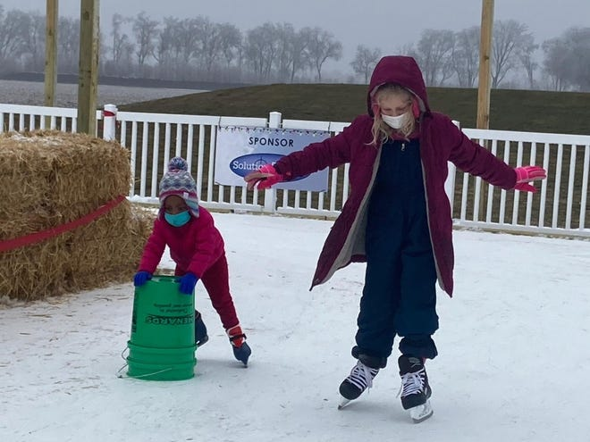 Evynn Wesley, 3, left, maneuvers around the Sangamon CEO LRS ice rink  alongside Maggie Aten, 10, of New Berlin. Aten was assisting Wesley, who had been to the rink once before and wanted to return, said her mother, Vyvyan Wesley. The ice rink is behind Scheels, 3801 S. MacArthur Blvd., and is open through at least Feb. 28. [Steven Spearie/The State Journal-Register]