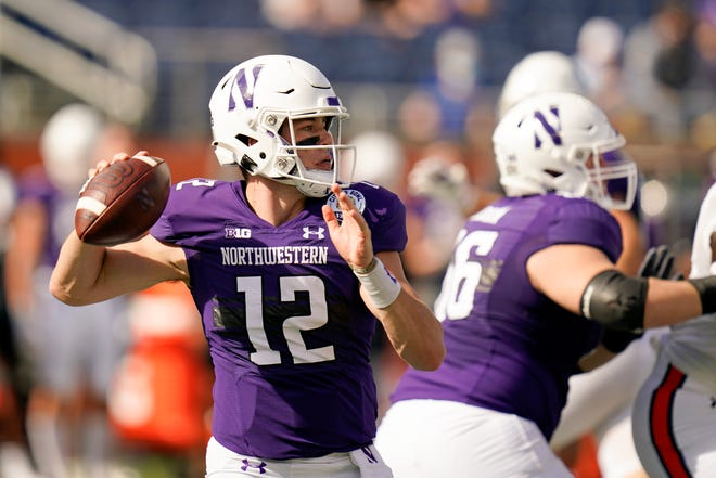 Northwestern quarterback Peyton Ramsey (12) looks for a receiver against Auburn during the first half of the Citrus Bowl NCAA college football game, Friday, Jan. 1, 2021, in Orlando, Fla.