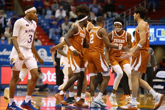 Texas players celebrate a 3-pointer by senior guard Matt Coleman III as Kansas freshman guard Dajuan Harris Jr. walks toward the bench in the second half of last Saturday's game in Lawrence. The Jayhawks lost 84-59, equaling their most lopsided defeat ever inside Allen Fieldhouse.