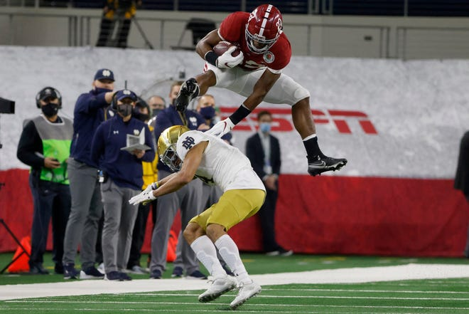 Alabama running back Najee Harris hurdles Notre Dame cornerback Nick McCloud as he carries the ball for a long gain in the first half of the Rose Bowl.