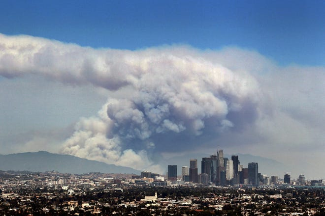 In this 2016 file photo, smoke from wildfires burning in Angeles National Forest fills the sky behind the Los Angeles skyline.