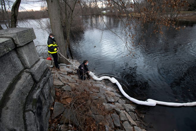 Concord firefighters Brett Mills (left) and David Nichols deploy an absorption boom into the Sudbury River, after a hydraulic spill on Nashawtuc and Musketaquid Roads in Concord, Jan. 2, 2021.
