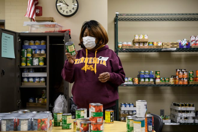 Volunteer Vanessa Brown sorts through canned goods donated by Tri-State Food Bank for the food pantry at Lincoln School in Evansville, Ind., Friday, Dec. 4, 2020.