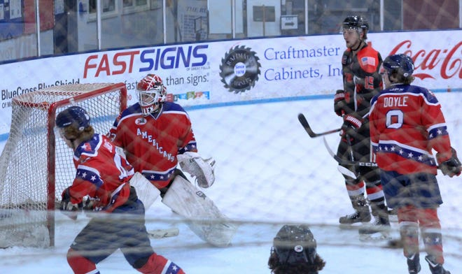 All eyes are on the puck after Great Falls Americans' goalie Trever Mellen steers away a shot by Butte's Randy Yeakley as Tommy Janes (front left) and Connor Doyle defend New Year's Eve at the Ice Plex.